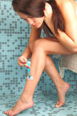 Beautiful girl shaving her legs with razor — Stock Photo
