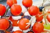 Small tomatos with mozzarella on skewer — Stock Photo