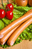 Sausage on green lettuce — Stock Photo
