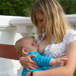 Young mother breastfeeding her son - Stock Photo