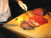 O processo de corte de carne assada. — Fotografia Stock