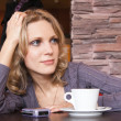 Young blonde in a cafe waiting for a call - Stock Photo