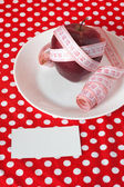 Red apple and measuring tape on a white plate on a red background and card — Stock Photo