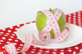 Green apple and measuring tape on a white plate on the red polka dot tablec — Stock Photo
