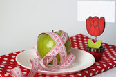 Green apple and measuring tape on a white plate and pin with a white leaf o — Stock Photo