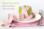 Green apple and measuring tape on a white plate and fork — Stock Photo