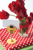 Bouquet of red tulips and clothespin with card for text — Stock Photo