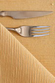 The fork, knife and yellow striped table cloth — Stock Photo