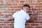 A handsome young man leaning against a brick wall — Stock Photo