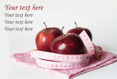 Three red juicy apples and measuring tape — Stock Photo