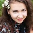 Photo: Portrait of beautiful young brunette with flowering branches