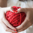 Big ball of red wool in the hands of a girl — Stock Photo