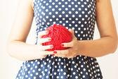 大红色羊毛的一个女孩手中的球 — 图库照片