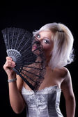 Young sexy girl with fan in corset look at you — Stock Photo