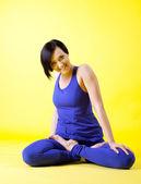 Beauty woman smile in lotos asana - blue on yellow — Stock Photo