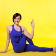 Woman sit in yoga pose - padmasana on yellow — Stock Photo