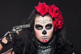 Young girl in day of the dead mask with gun — Stockfoto