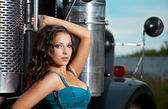 Young pretty girl in jeans stand near steel truck — Stock Photo