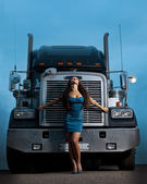 Young pretty girl posing before huge cargo truck — Stock Photo