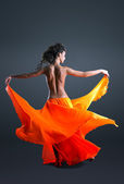 Beauty girl with naked spine dance in orange cloth — Stock Photo