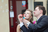 Just married couple blow bubbles — Stock Photo