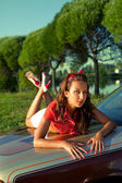 Young woman lay on retro car in summer sunset — Stock Photo