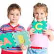 Boy and girl holding letters — Stockfoto