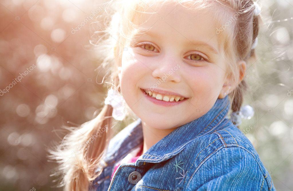 可爱的小女孩,在一个公园特写镜头微笑