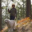 Woman walking Maremma dog in the trees - Stock Photo