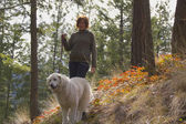 Woman walking Maremma dog in the trees — Stock Photo