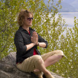 Woman meditating at a lake - Stock Photo