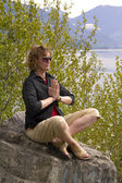 Woman meditating at a lake — Stock Photo