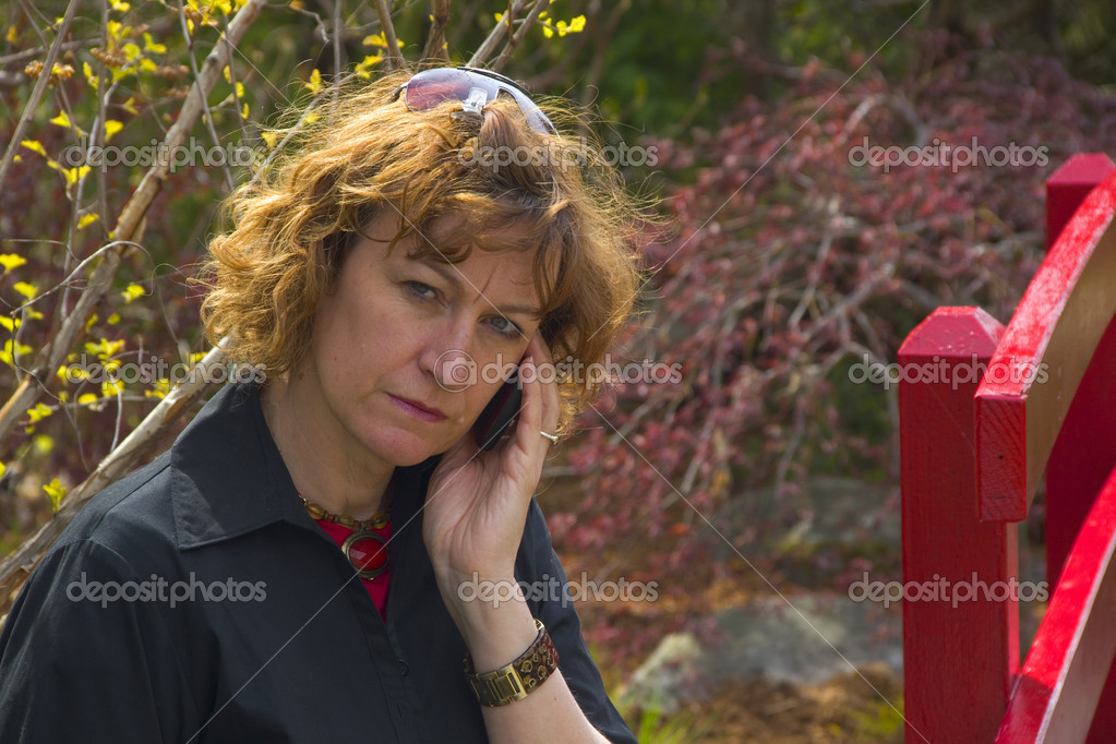 Woman in a park looking very serious on a cell phone — Stock Photo #5670842