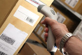 Man with barcode reader works on warehouse — Stock Photo