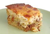 Isolated piece of pastitsio on a dish — Stock Photo
