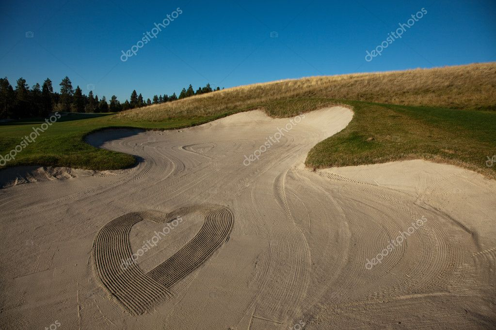 The shape of a heart made by a rake in a sand trap at a golf course. — Stock Photo #5543438