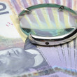Magnifying glass on money background — Stock Photo