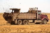 Truck spreading manure on a Saskatchewan stubble field — Stock Photo
