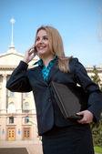 Die junge geschäftsfrau spricht per telefon — Stockfoto