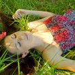 Stock Photo: Young girl lies in grass