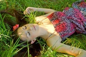 The young girl lies in a grass — Stock Photo