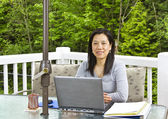 Lady working at home on outdoor patio — Stock Photo
