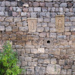 Small cross-stones on a wall — Stock Photo