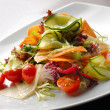 Salad with fresh vegetables, tomatoes and avocado on plates — Stok fotoğraf