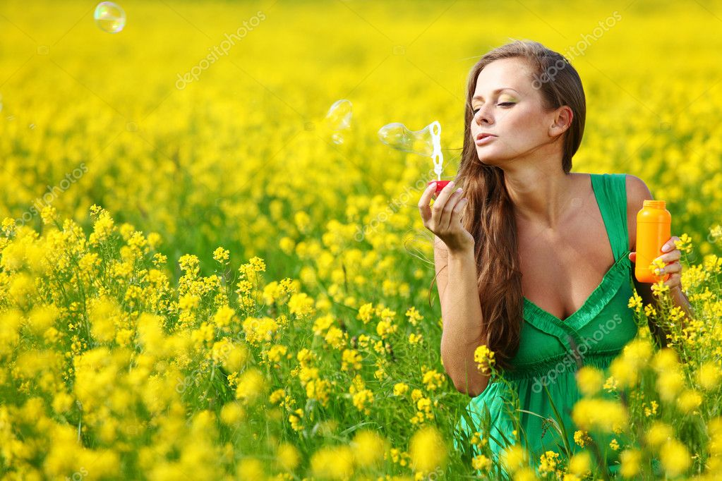 Woman start soap bubbles on yellow flower field — Stock Photo #6649685