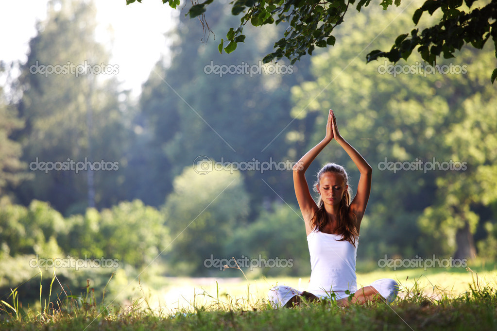 Yoga woman on green grass in lotus pose  Stock Photo #6649781