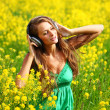 Stock Photo: Womin headphones on oilseed field