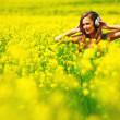 Woman in headphones on oilseed field — Stock Photo