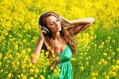 Woman in headphones on oilseed field — Stock Photo