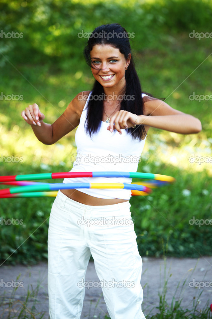 Woman rotates hula hoop on nature background — Stock Photo #6650025